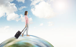 Girl in pink shirt walking on the globe with sky. Portrait of woman in pink shirt with black suitcase walking on huge globe. Concept of tourism and travelling Stock Photos