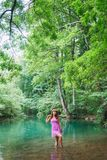 Girl in a pink short dress walks on a river in the forest royalty free stock image