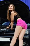 Girl in pink shorts with wrenches near a black car with an open royalty free stock photos