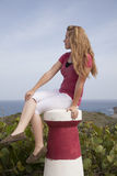 Girl in pink sit on small lighthouse Stock Images