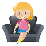 Girl in pink sitting on gray sofa Stock Images