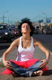 Girl in pink skirt meditates on highway middle royalty free stock image