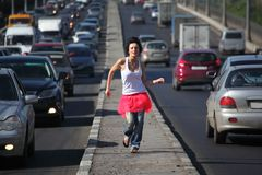 Girl in pink skirt runs on highway middle Stock Images