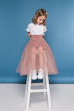 Girl in pink skirt sitting on ladder and looking down Stock Photo