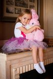 Girl in pink skirt with soft toy Royalty Free Stock Photos