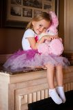 Girl in pink skirt with soft toy Stock Photo