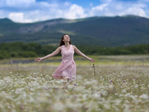 Girl in pink sleeveless dress walks on meadow of chamomile. Girl in chamomile field with arms outstretched. Young woman in pink sleeveless dress walks on meadow Stock Photos
