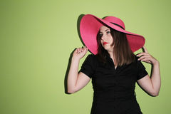 Girl with pink straw hat on green background Stock Photos