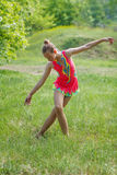 Girl in pink suit doing gymnastics in forest. Gymnast-girl is exercising at the green meadow stock photography