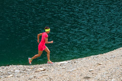 Girl with pink suit runs near a lake Stock Image