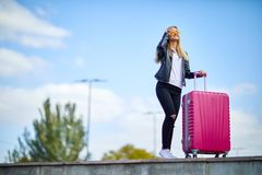 Girl with a pink suitcase on a background of a beautiful blue sky royalty free stock image
