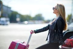 A girl with a pink suitcase is sitting on the trunk of a car Royalty Free Stock Photos