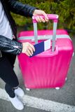 A girl with a pink suitcase stands on the street close up Royalty Free Stock Photos