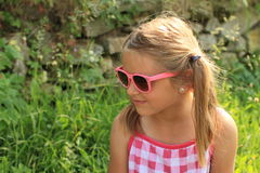 Girl in pink sun glasses. Little girl in pink and white dress and pink glasses Stock Photo