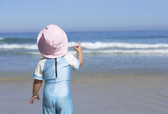 Girl (2-4) in pink sun hat standing on sandy beach, looking at horizon over sea, rear view Stock Images