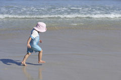 Girl (2-4) in pink sun hat walking on sandy beach near water's edge, profile Stock Image