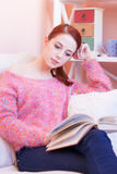 Girl in pink sweater with book Stock Photo