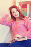 Girl in pink sweater with book. Redhead girl in pink sweater with book sitting on sofa at home Stock Photo