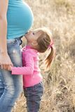Girl in Pink Sweater and Grey Jeans Kissing Tummy of Pregnant Woman in Blue Shirt and Blue Denim Jeans Royalty Free Stock Photo