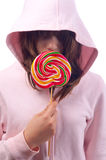 Girl in the pink sweater holds big lollipop Royalty Free Stock Photos