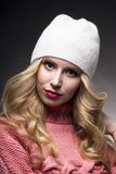 The girl in a pink sweater and a white cap on a gray background Stock Photos