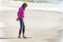 Girl in pink sweatshirt draws in sand with toe Stock Photo