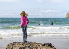 Girl in pink sweatshirt looks out at surfers Royalty Free Stock Photography