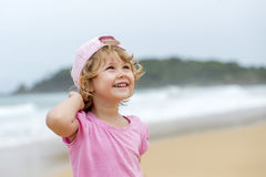 Girl in pink at th ebeach. Girl in pink shirt and hat at the beach Stock Photo