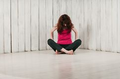 A girl in a pink top, sitting cross-legged on the floor, light b. A pretty long-haired girl in a pink top, sitting cross-legged on the floor, head down, light Royalty Free Stock Photos