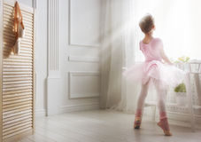 Girl in a pink tutu. Cute little girl dreams of becoming a ballerina. Child girl in a pink tutu dancing in a room. Baby girl is studying ballet Royalty Free Stock Photo