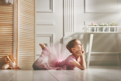 Girl in a pink tutu. Cute little girl dreams of becoming a ballerina. Child girl in a pink tutu dancing in a room. Baby girl is studying ballet Stock Photography