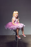 Girl in pink tutu, studio sitting a chair Stock Image