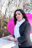 Girl and pink umbrella. The girl leans on the parapet, near stand a pink umbrella Stock Image