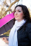 Girl and pink umbrella. The girl leans on the parapet, near stand a pink umbrella Stock Images