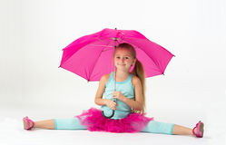 A girl with a pink umbrella do the splits Stock Images