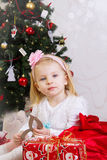 Girl in pink under Christmas tree Royalty Free Stock Images