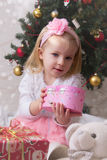 Girl in pink under Christmas tree Royalty Free Stock Photo