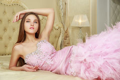Girl in pink wedding dress on the bed.  Stock Photography