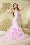 Girl in pink wedding dress staying on the bed.  Stock Photography