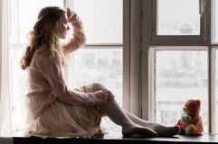 Girl in pink by the window Royalty Free Stock Image