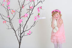 Girl in a pink wreath and a pink dress with a bird on a flowerin. G tree. Laughing and holding her cheeks Royalty Free Stock Photo