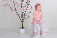 Girl in a pink wreath and a pink dress with a bird on a flowerin. G tree. smiling Royalty Free Stock Photography