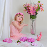 Girl in a pink wreath and a pink dress is smiling and sitting on. The floor Stock Photo