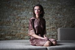 Girl PinUp with brunette hair and retro make-up with red lips in a bathrobe on a dark background. Royalty Free Stock Images