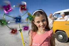 Girl (7-9) with pinwheel on beach, grandparents and camper van in background, smiling, portrait Royalty Free Stock Photo