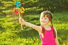 Girl with pinwheel Stock Images