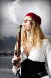 Girl pirate blows a smoke from a old pistol royalty free stock images
