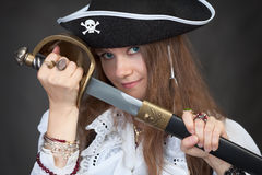 Girl in pirate hat with a sabre in hands Stock Image