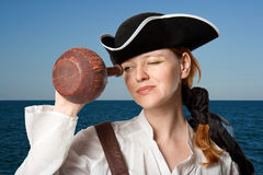 The girl-pirate looks in a jug against the sea. The girl-pirate in a cocked hat against the sea looks in a jug Stock Images