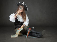 Girl the pirate looks through a magnifier Stock Photos